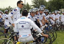 """FILE - This Wednesday June 4, 2009, file photo shows a pack of convicts, joined by their jailers, preparing to take the start from Villeneuve d'Ascq to Valenciennes, northern France, of the prologue of the """"Tour de France Penitentiaire"""" for the jailed. Most days, they live behind bars. But last week, a pack of convicts, joined by their jailers, a police escort and a string of support vehicles, embarked upon the inaugural two-week, 2,200 kilometer cycling trek across the Gallic countryside, organized by French prison administrators. (AP Photo)"""